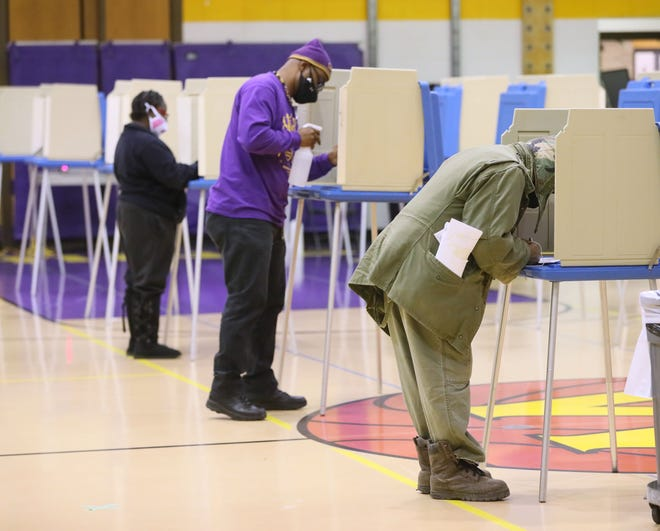 People mark their ballots at Washington High School in Milwaukee on Election Day, November 3, 2020, as a poll worker cleans each voting booth after each voter leaves.