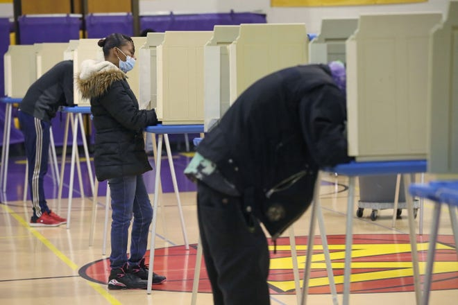 People mark their ballots at Washington High School in Milwaukee on Election Day, November 3, 2020.
