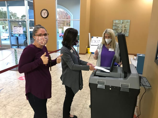 Sadie Fisher (far left) shoots two thumbs up towards the camera as Baxter County Clerk Canda Reese (middle) and election worker Lyn Keaster feed Fisher's ballot into the tabulator at the First United Methodist Church early voting site on Monday evening. Fisher was the final citizen to early vote at the site, completing her ballot shortly after 5 p.m.