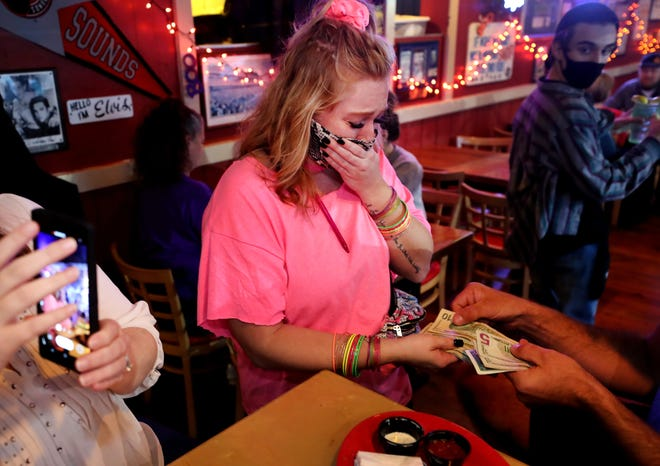Madelynne Bogle, a server at Toot's, reacts on Thursday, Oct. 29, 2020, as she is given money by Tyler Black and wife Angela Black, as part of the Facebook Group Tipping in the Boro, that was started to garner money to pool efforts and bless servers locally.