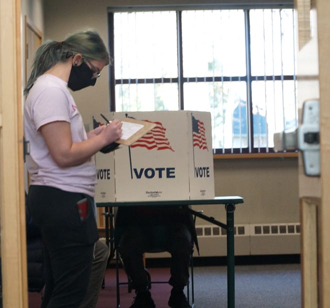 A voter fills out a ballot application card at the Westland Library on Nov. 3, 2020.