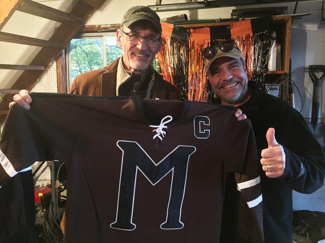Market manager Walt Gajewski shows off a special gift he received from volunteer Kevin Christiansen (right) after the Oct. 31 farmers market.