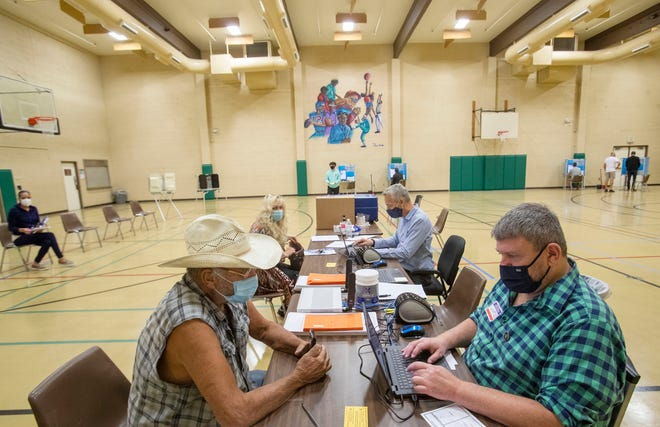 At left John Cadenhead, 74, registers to vote at the James O. Jessie Desert Highland Unity Center on November 3, 2020. Cadenhead was able to vote using a provisional vote.