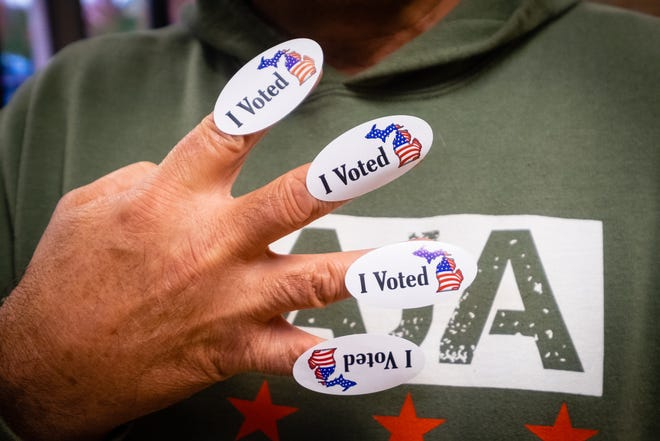 Rich Pohman, of Port Huron, collected four 'I Voted' stickers after casting his ballot Tuesday, Nov. 3, 2020, at First United Methodist Church in Port Huron. The stickers represent Pohman's hope for 'four more years' for President Donald Trump.