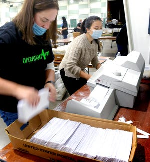 York County employees Heather Strausbaugh, left, and Victoria Kwok operate an envelope opener while sorting ballots at the York Fairground's Memorial Hall Tuesday, Nov. 3, 2020. About 100 county employees volunteered on their day off to help process ballots. Bill Kalina photo