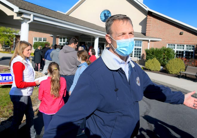 Incumbent congressman Scott Perry talks to the media while waiting in line with his wife Christy, and their daughters Mattea, 9, and Ryenn, 11, right, at the polls at Monaghan Presbyterian Church in Dillsburg Tuesday, Nov. 3, 2020. Perry is defending his seat against Pennsylvania Auditor General Eugene DePasquale. Bill Kalina photo