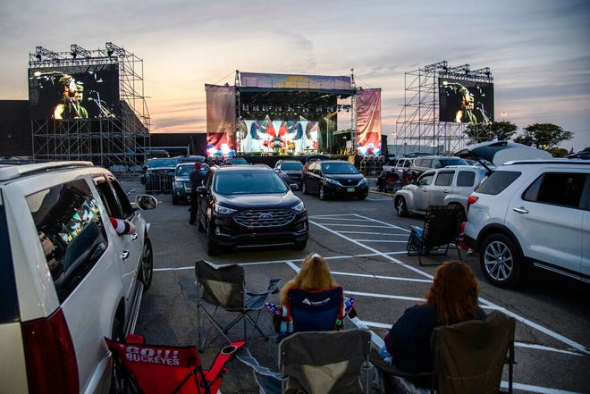Attendees sit next to their car as J.R. Moore & Zack Mack perform at the Drive-In at Westland Mall in Columbus, Ohio on Oct. 10, 2020. After a historic season, winter is coming at the drive-in.