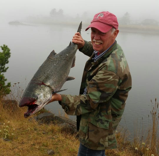 Ron Bryant of Mt. Angel hoists a hefty Chinook salmon that he caught at what's known as the poggy hole.