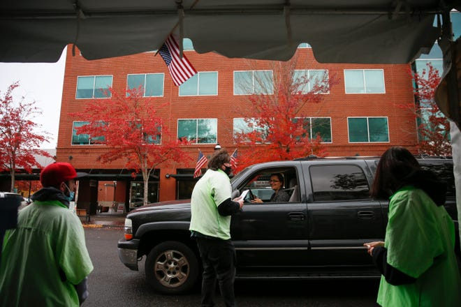 Drivers line up to drop off their ballots outside the Marion County Courthouse on Tuesday in Salem.