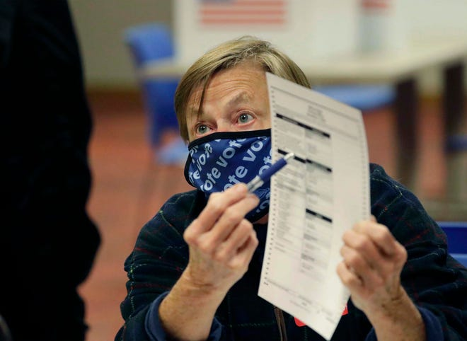 Mary Beth Martin points out areas on a blank ballot for a voter at Mead Public Library, Nov. 3, 2020, in Sheboygan.