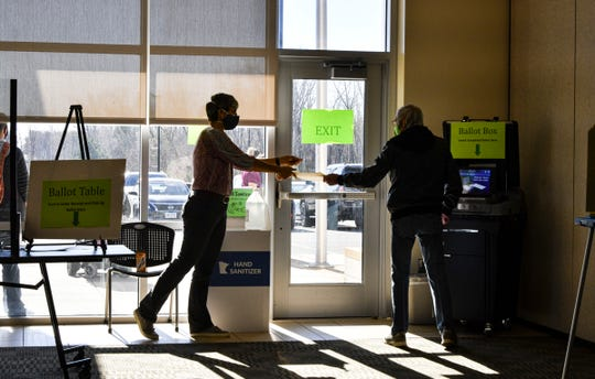 An election worker takes a cover folder from a voter after he casts his ballot Tuesday, Nov. 3, 2020, at the Sauk Rapids Government Center.