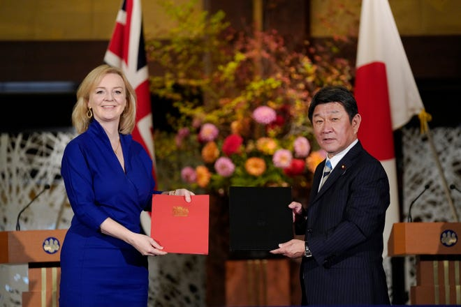 British International Trade Secretary Liz Truss, left, and Japanese Foreign Minister Toshimitsu Motegi exchange agreement documents for economic partnership between Japan and Britain at Iikura Annex of the Foreign Ministry in Tokyo, Friday, Oct. 23, 2020.