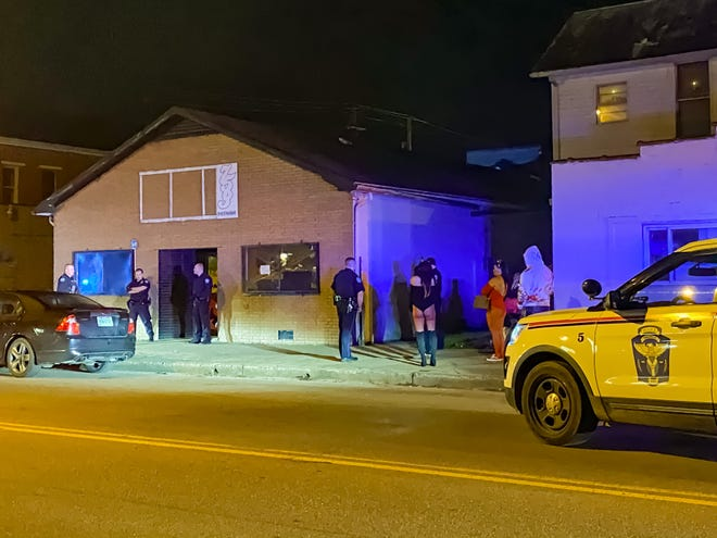 Police execute a warrant Saturday night during a Halloween party at an after-hours bar on Putnam Avenue.