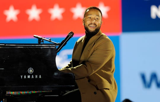 John Legend plays the piano while driving out of a voting rally that involves Democratic vice presidential candidate, Sen. Kamala Harris, D-Calif., Monday, November 2, 2020, in Philadelphia.