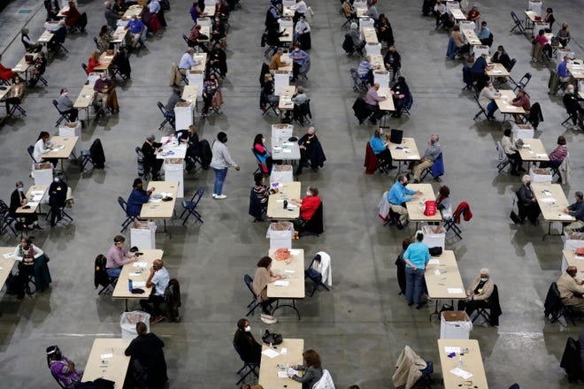 Volunteers for counting absentee ballots sit two to a table across the floor of FedExForum early on Election Day, Tuesday, Nov. 3, 2020, in Memphis, Tenn.