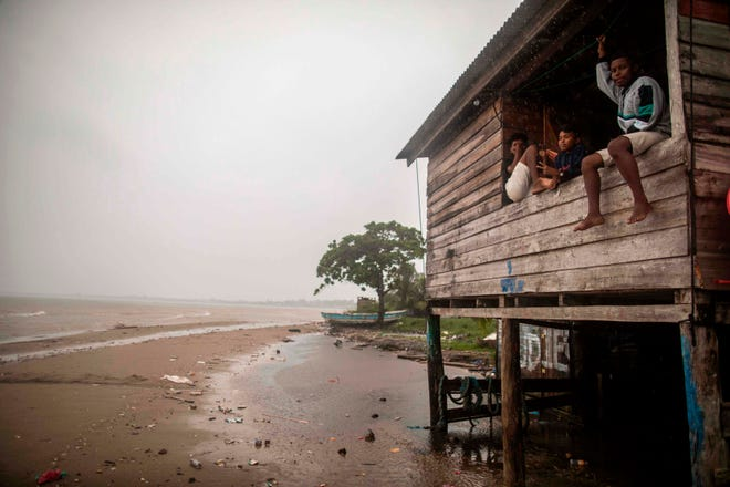 Children sit on a beach house window as Hurricane Eta approaches in Bilwi, Puerto Cabezas, Nicaragua, on Nov. 2, 2020. Eta rapidly intensified to a Category 4 hurricane on Monday as it bore down on the Caribbean coast of Nicaragua and Honduras, threatening the Central American countries with catastrophic winds and floods.