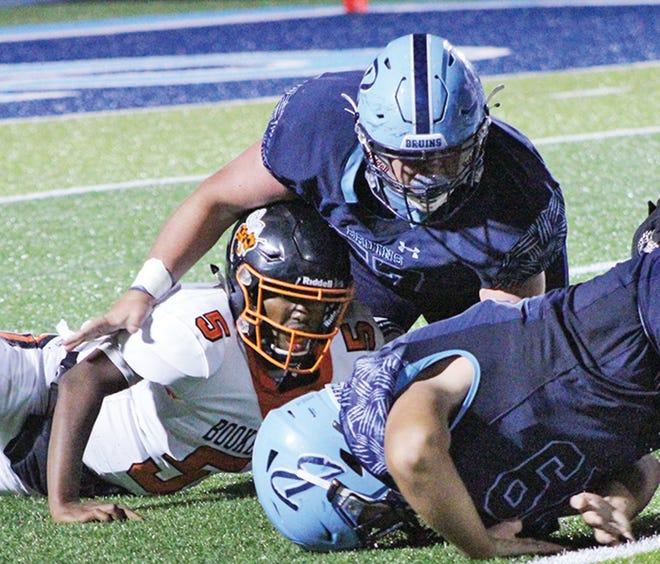 Bartlesville High and Tulsa Washington players go after a loose ball during varsity football action earlier this season.