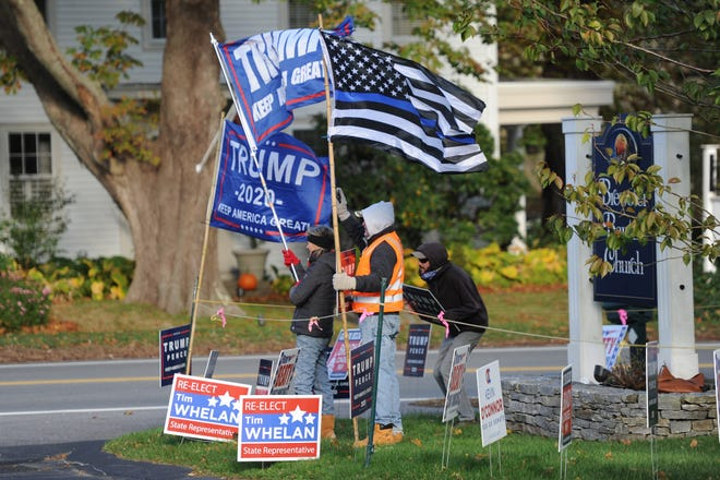 Brewster Republican Committee member Paula Miller, Vice Chairman Adam Lange and member Dan Powers, from left, wave flags and signs in support of President Donald Trump at the entrance to the polls at Brewster Baptist Church.