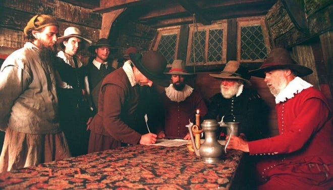Actors recreate the signing of the Mayflower Compact yesterday morning aboard the Mayflower II at the Provincetown waterfront.