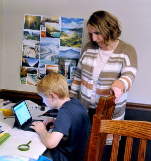 Angie Bos helps her son Liam van Doorn, a fifth-grader at Edgewood Middle School in Wooster, with his online learning project. He planned to draw the United States and color sections according to what country first colonized the area.