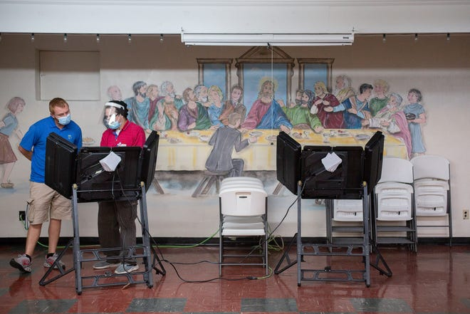 Election official Dennis Ellington, right, assists Paul Stevens, left, as he prepares to cast his ballot inside Cumberland Presbyterian Church in Columbia, Tenn, on Election Day, Tuesday, Nov. 3, 2020.
