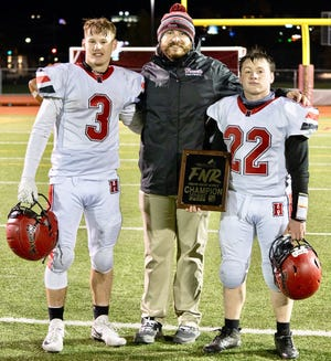 Honesdale's Paul Russick is all smiles after notching the first win of his varsity coaching career. He's pictured here with star running backs Jacob Orrick and Connor Schmitt after the Hornets' 42-20 victory over West Scranton.