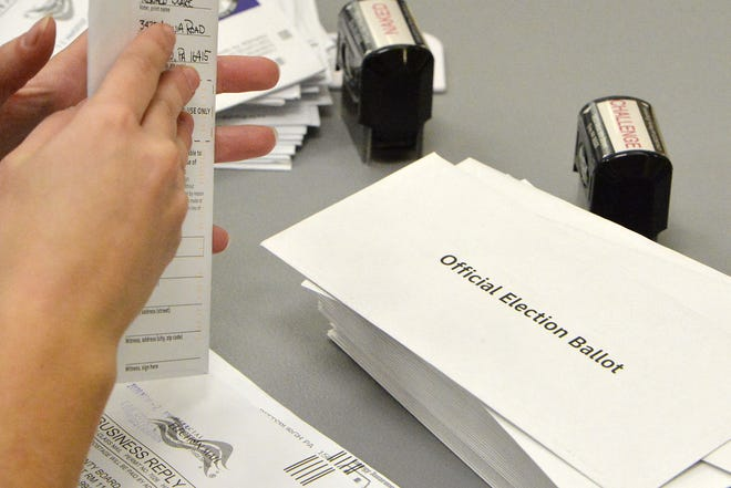 Election officials open mail-in ballots at the Erie County Courthouse on Nov. 3 in Erie. Election officials have purged about 25,000 inactive voters from its rolls, as required  by law.