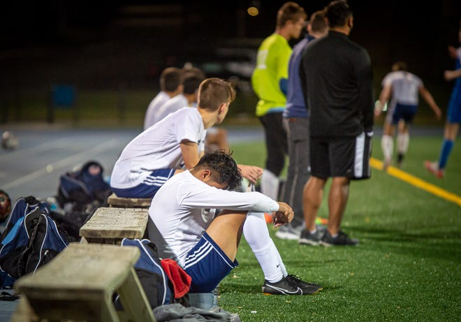 Truman senior Alan Romero, front, sits in front of the bench dejectedly during the final minute of the Patriots' 7-1 loss to state power Rockhurst in the Class 4 District 14 championship Tuesday at Rockhurst. The Patriots lost to the Hawklets in the district final for the sixth straight year.
