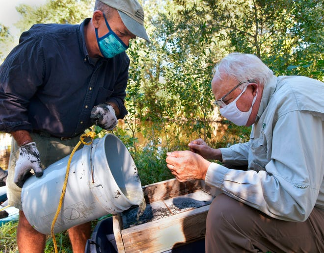 Jacksonville University biology professor Dan McCarthy (left) pours water and sediment from McCoys Creek through a sifter while Quinton White of JU's Marine Science Research Institute watches for items to inventory.