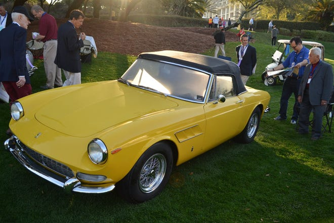 Judges take a look at Jacksonville resident Rodolfo Junco de la Vega's (right)  yellow Ferrari 275 GTS at the 2015 Amelia Island Concours. The car is the prototype for the classic convertible model.