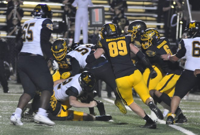 The Yellow Jackets converge to sack Frisco Memorial's Charlie Flowers during Denison's victory in District 7-5A (II) play at Munson Stadium.