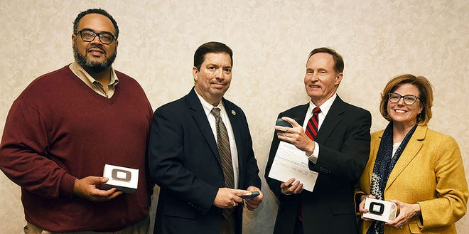 Bob Griffin, second from right, president of the Rotary Club of Kinston, gets a look at a hotspot device while delivering a grant check to Lenoir County Public Schools and, from left, Assistant Superintendent Nicholas Harvey II, Superintendent Brent Williams and Associate Superintendent Frances Herring. The Kinston club and Rotary District 7730, of which the Kinston club is a part, each awarded LCPS grants totaling $4,921 for the purchase of hotspots to help students connect to the internet. [CONTRIBUTED PHOTO]