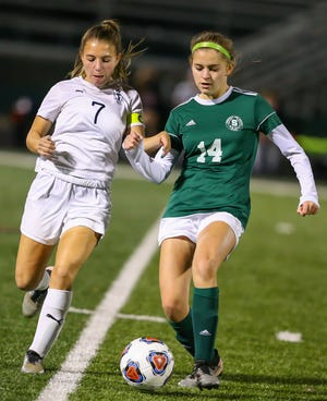 Twinsburg captain Sami DiMuzio battles for the ball with Strongville's Maggen McFadden during the Tigers' 4-0 loss to the Mustangs Nov. 3 in a Division I regional semifinal game at Strongsville.
