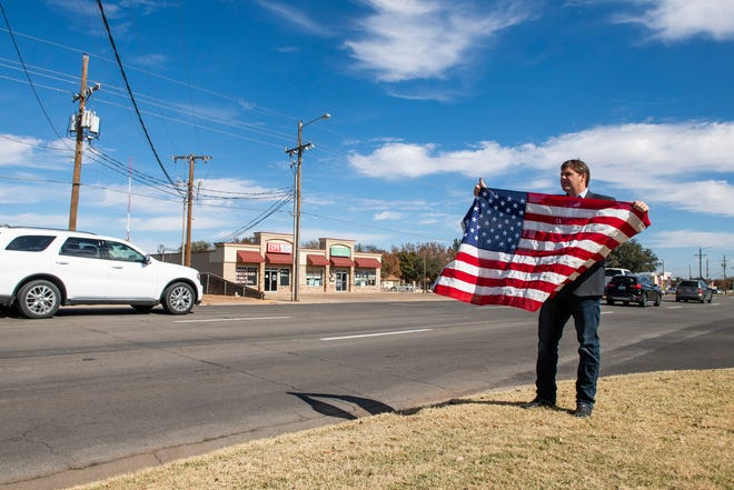 U.S. Rep. Jodey Arrington holds a flag while campaigning at Calvary Baptist Church on Tuesday, Nov. 3, 2020, in Lubbock, Texas.