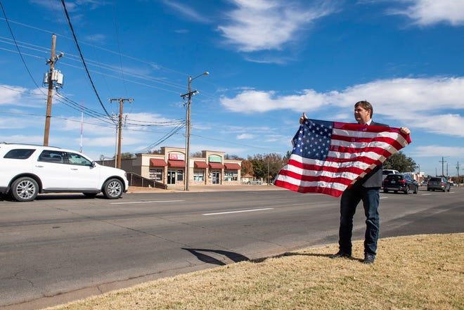 U.S. Rep. Jodey Arrington stands outside a voting location Tuesday with a flag of the United States.