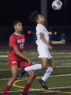 Moberly junior forward Charez Nichols leaps to settle a 50/50 ball using his chest Tuesday while being defended by Mexico's Daeye Miller (No. 15) Tuesday during a Class 2 District 6 semifinal. The Spartans won 2-1 in double overtime to advance and play Fulton in Thursday's championship game.