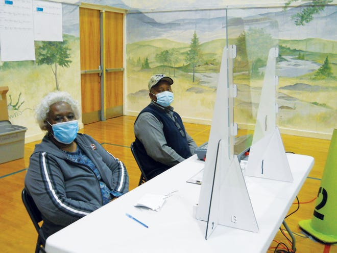 Henrietta Caldwell and Thomas Moton, wearing masks and behind a plexiglass shield, work at the Woodland Elementary School precinct Tuesday.