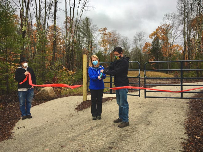 Tanja Schoenbrod, vice president of Arundel Conservation Trust, and Matt Cooper, chair of Bike Trail Committee, cut the ribbon to open the trails Oct. 17.