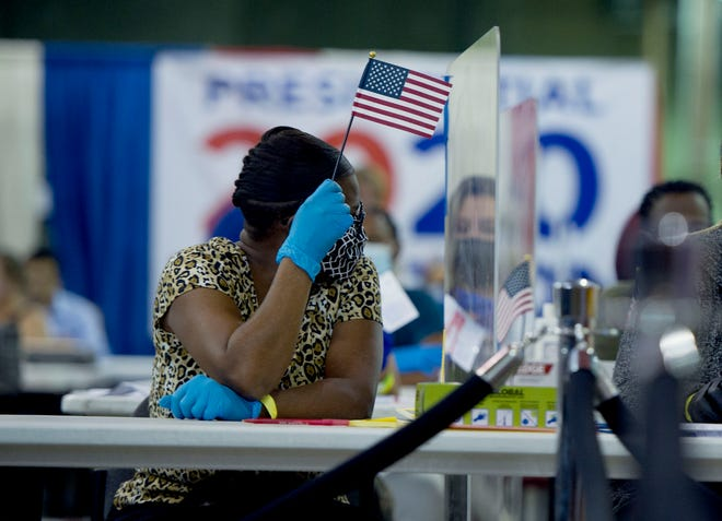 Palm Beach County election workers do their jobs Tuesday behind COVID-19 safety barriers at the elections counting center in Riviera Beach.