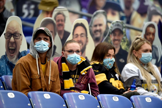 Specators wear face masks to protect against COVID-19 during the first half of Sunday's game between the Baltimore Ravens and the Pittsburgh Steelers, in Baltimore.