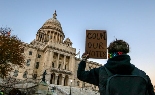 A protester with the nonprofit Direct Action for Rights and Equality holds a sign at Wednesday's rally in front of the State House, calling for all ballots to be counted in the presidential election.
