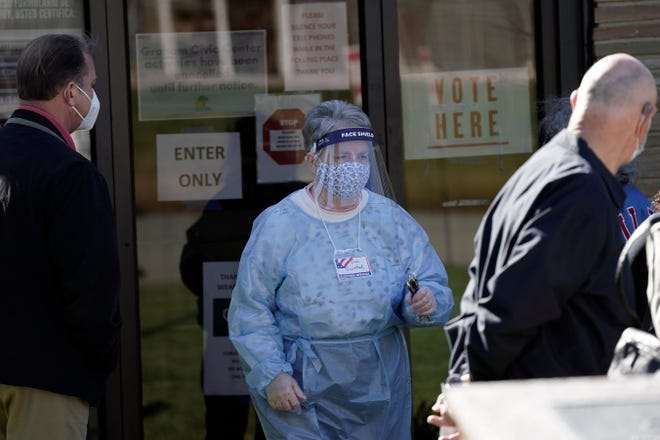 Poll worker Dina Grinstead assists voters at the Graham Civic Center polling location in Graham, N.C., Tuesday, Nov. 3, 2020. (AP Photo/Gerry Broome)
