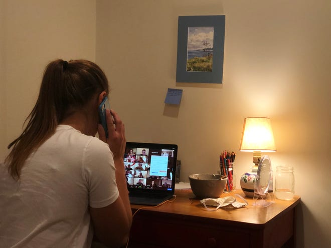 Ainsley Clapp works the phones on behalf of the Iowa Democratic Party from her Providence bedroom.