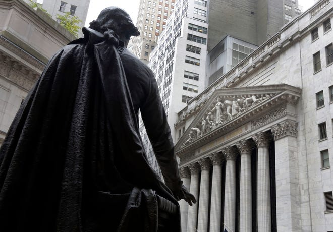 FILE - In this Oct. 2, 2014, file photo, a statue of President George Washington on the steps of Federal Hall faces the facade of the New York Stock Exchange.  U.S. stock futures and markets around the world are mostly holding steady or ticking higher early Wednesday, Nov. 4, 2020, but that's only after they spun through another election night dominated by surprises and sharp swings.  (AP Photo/Richard Drew, File)