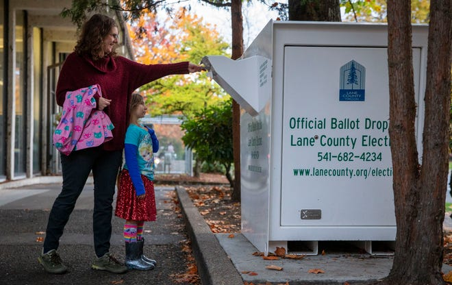 Katie Petersen votes over her daughter Lilyanah Sutton at the Lane County Elections drop box on  Nov. 3, 2020, in Eugene.  Lane County has experienced a strong voter turnout for the 2020 election.