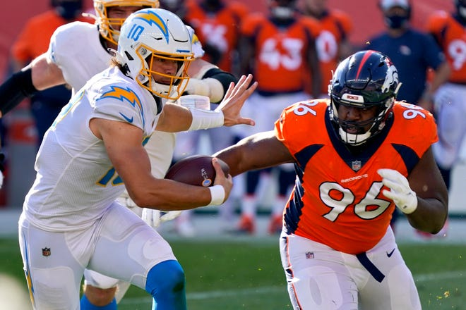 Los Angeles Chargers quarterback Justin Herbert tries to run away from Denver defensive end Shelby Harris (96) during the first half of Sunday's game in Denver.