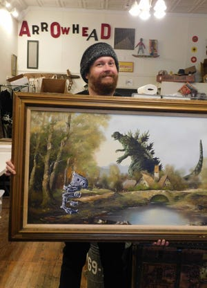 """David Sherrill with one of his paintings. He he adds """"Star Wars"""" and horror-movie figures to motel-art landscapes."""