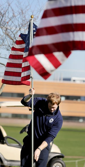Ryan Clevenger, a Plain Township Firefighter / EMT , sets up a one of the 200 flags on display in Veterans Park in Plain Township.