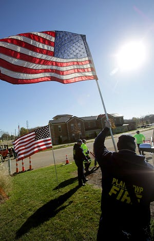 Plain Township Firefighter/ Paramedic Ryan Jones places one of the 200 flags on display at Veterans Park in Plain Township on Wednesday morning.
