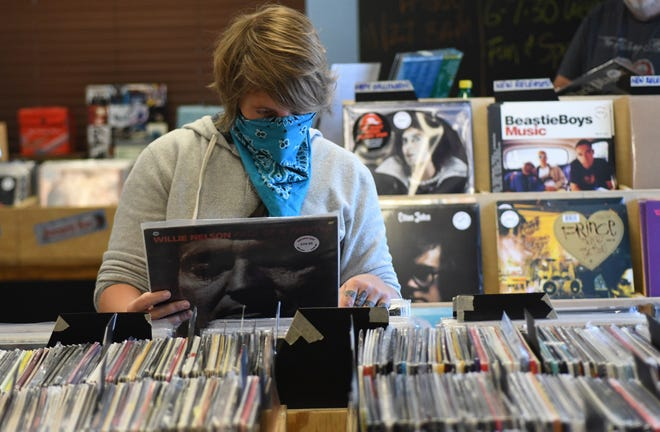 Brittanie Smith looks through records at Record Bar in Wilmington N.C., Wednesday, November 4, 2020. The store opened in December of 2019 and acquired the name from the chain that once had over 150 stores.     [MATT BORN/STARNEWS]
